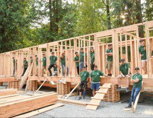 chnw team posing in framework of veteren village community buildings